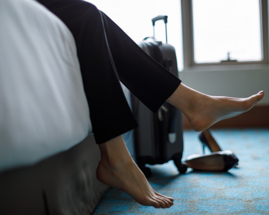 A woman kicks off her shoes while sitting on a bed