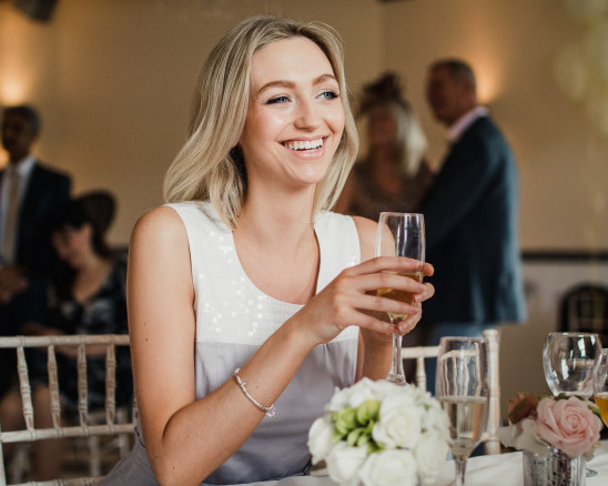 A Bridesmaid smiles holding champagne