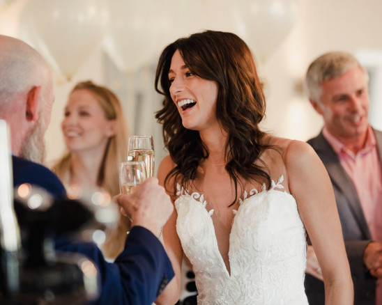 A bride laughs while toasting with her guests
