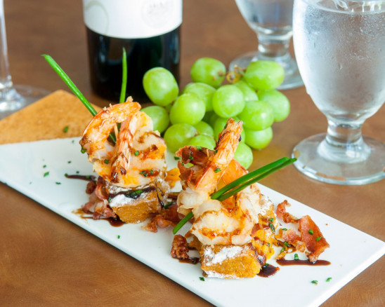 A shrimp dish next to grapes and a glass of water