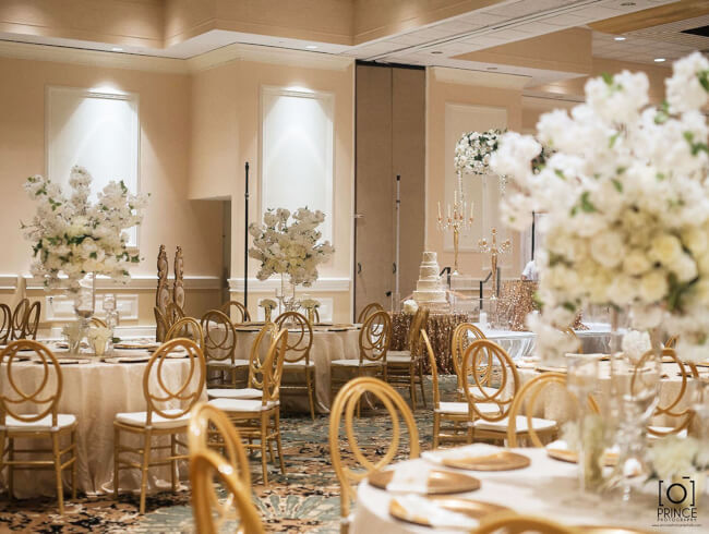 Gold designer chairs are set at tables with white mantles and gold plates