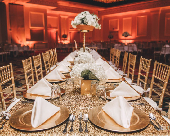 Bronze plates are set at a long wedding table leading up to a floral centerpiece