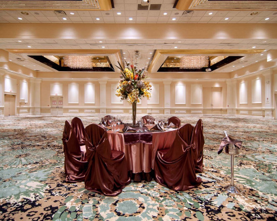 A small private dining table is elegantly draped in maroon and a champagne stand is set nearby