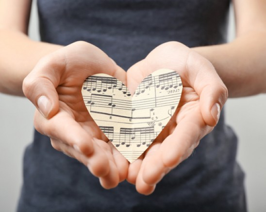 hands holding paper heart with musical notes