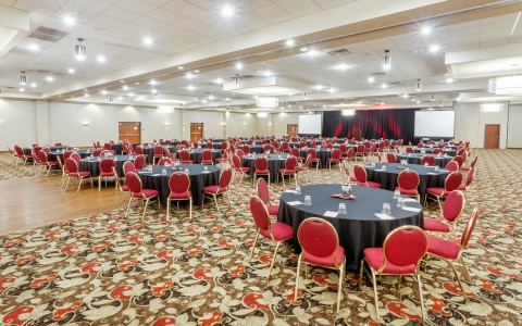 Large events space with circle tables and red chairs