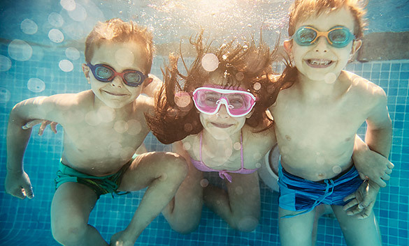 three kids under the water in a pool smiling with goggles on