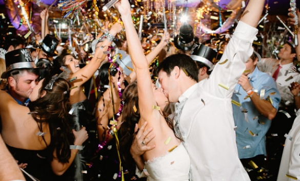 two people kissing with confetti and others kissing on NYE