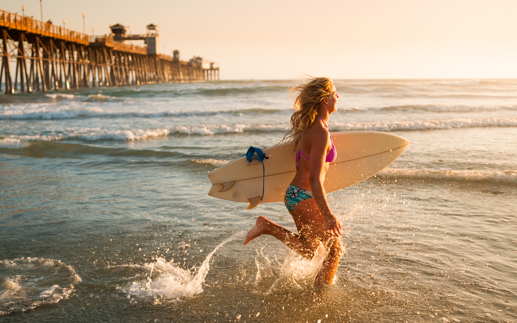 a woman on the beach with a surfboard