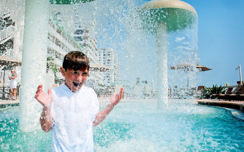 Boy standing in a pool under water falling