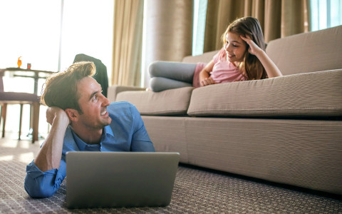 Man in front of a laptop smiling up at his daughter on the couch