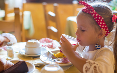 Young girl drinking juice and eating breakfast