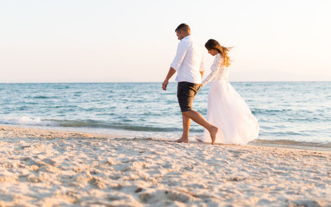 Bride and Groom walking down the beach