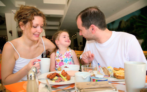 Man and woman with their daughter at breakfast table