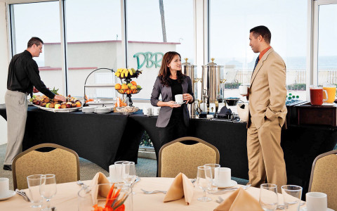 Man and woman talking beside a buffet table