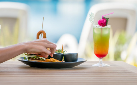 Tropical drink and sandwich on a wooden table