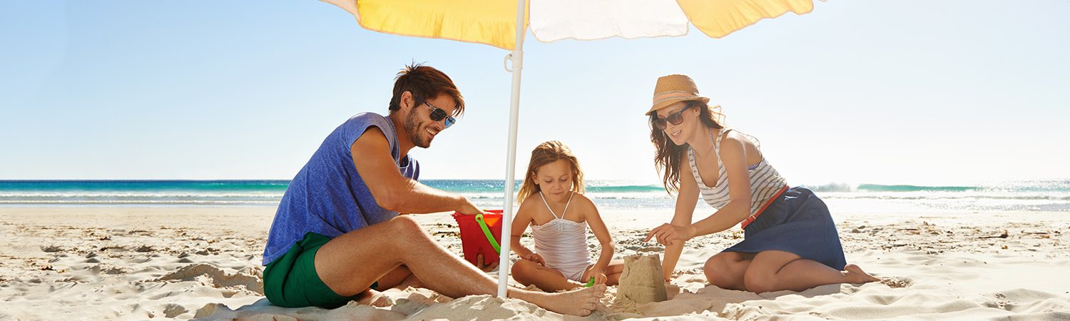 Family on beach sitting under a yellow and white umbrella