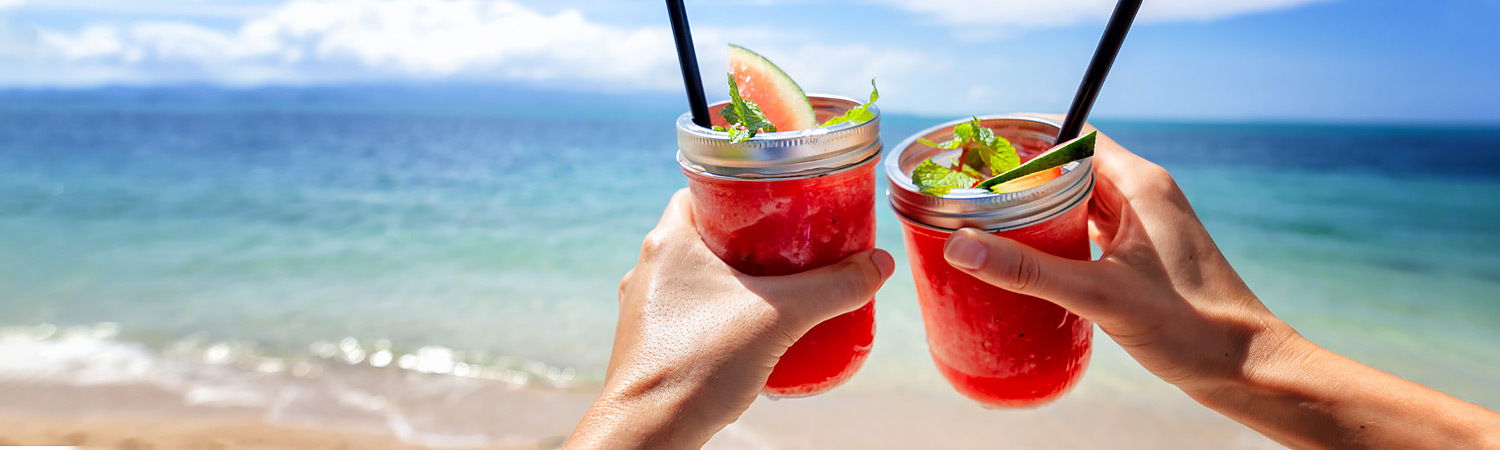 two people cheering drinks in front of beach