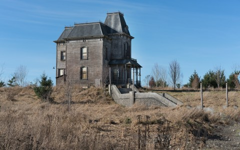 Abandoned Victorian home on desolate field