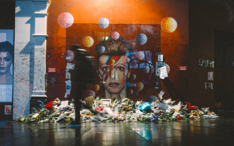 David Bowie memorial a mural of Ziggy Stardust with flowers laid in tribute