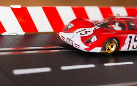 Red and white slot car on race track