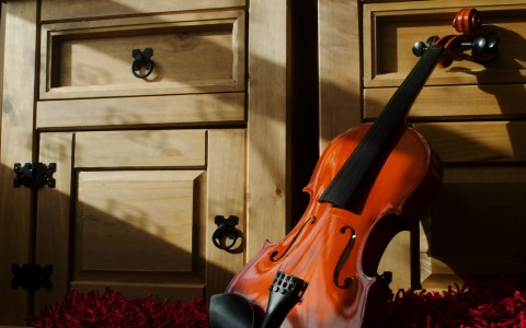 Violin on red frayed carpet leaning against cabinet