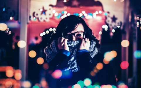 Young woman looking at viewer and wearing chunky glasses and playfully gripping scarf over her mouth surrounded by Christmas lights