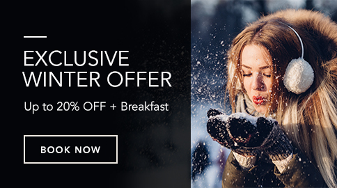 Exclusive Winter Offer: Up to 20 percent off plus breakfast with photo of a women wearing warm clothes and blowing towards the snow in her hand