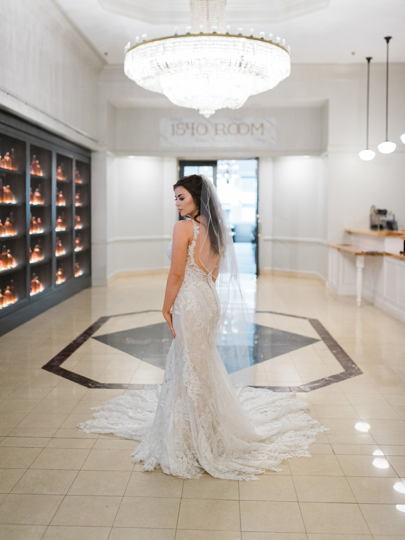 a bride taking pictures in her wedding gown in the lobby