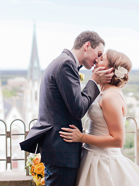 a bride and groom kissing on the balcony