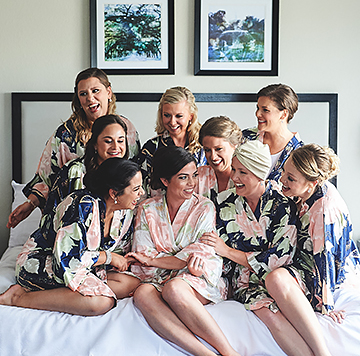 a bride and her bridesmaids on a hotel bed