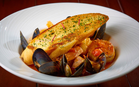 Dish with clams and slice of garlic bread