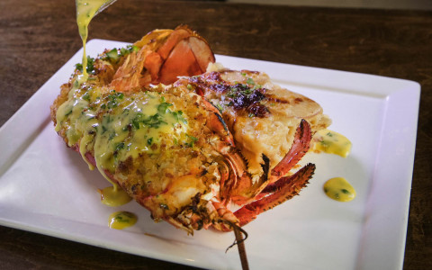 Lobster on dish being drizzled with yellow sauce