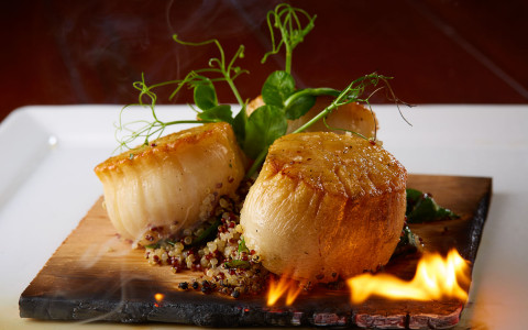Scallops being cooked over fire board