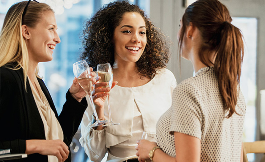 Three women talking with glass of champagne in hand