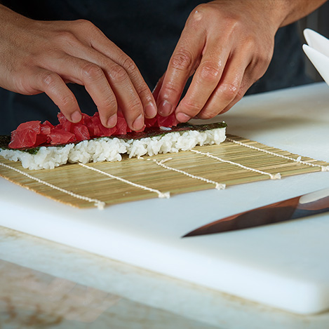 Close up of hands rolling sushi