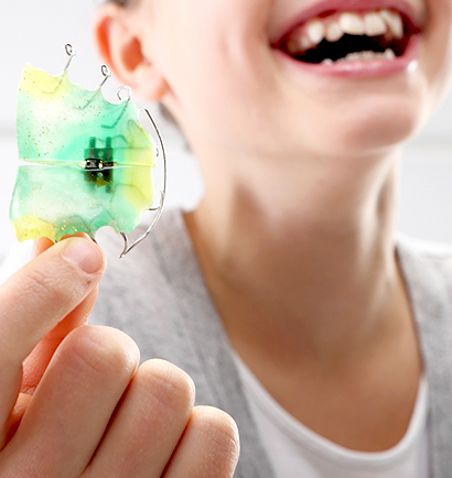 Little girl smiling as she holds her expander
