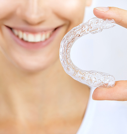 Woman holding invisalign mold