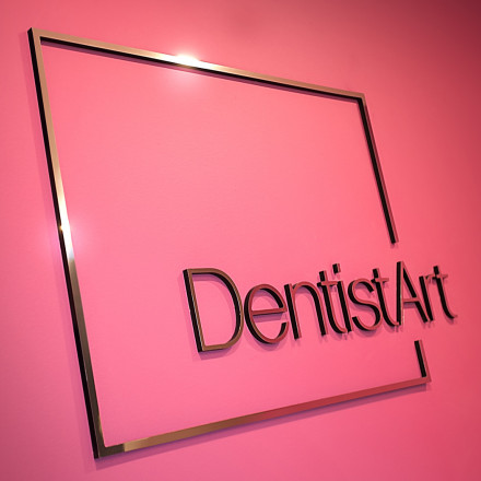 Dentist Art logo on magenta wall