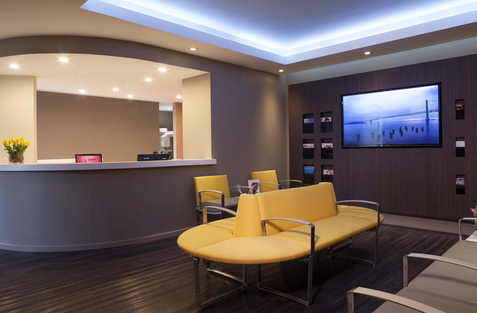 Lobby with yellow chairs, tv & front desk