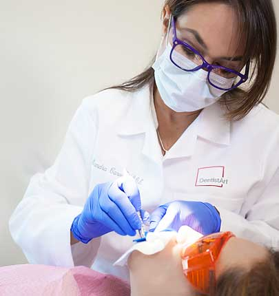 Doctor with mask working on young girl's teeth