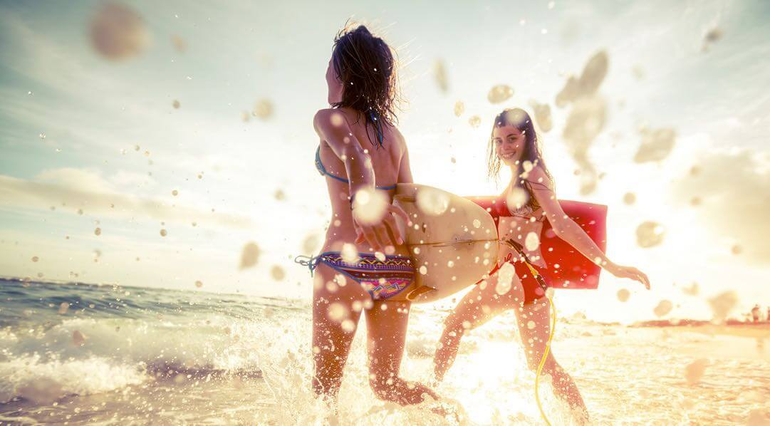 Two women with surfboards running into the water