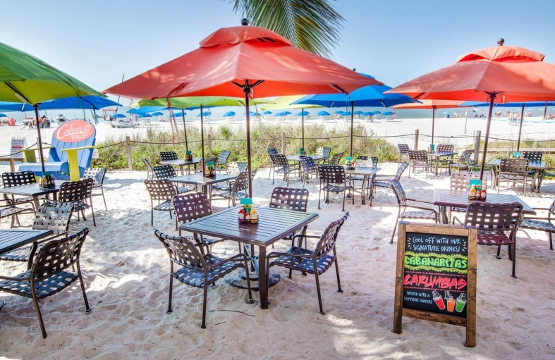 Chalk board offering Cabanaritas next to metallic tables & chairs with umbrellas outside on sand