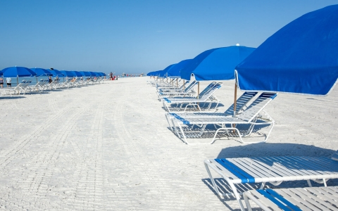 Lounge chairs on sand with blue umbrellas