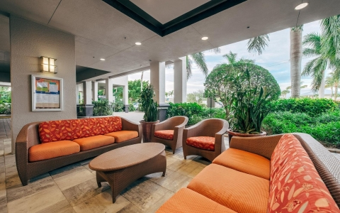 Outdoor lobby area seating with wicker couches & bright cushions