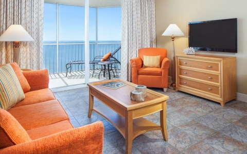 In room living space with orange couches, wooden coffee table, dresser, TV & balcony