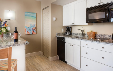 In room full kitchen with granite countertops, white cabinets, wooden flooring & appliances