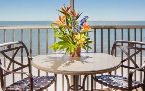 Close up of table with two chairs & tropical flower arrangement on in room balcony
