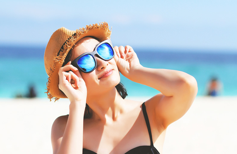 Woman wearing hat & holding sunglasses on face