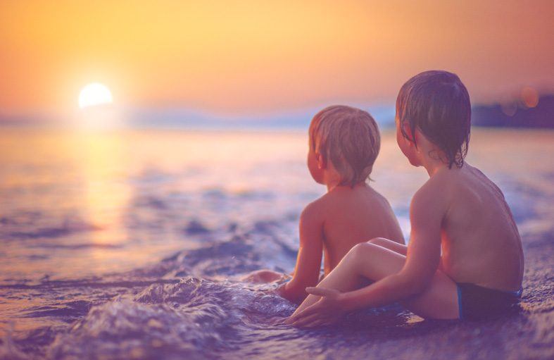 Two small boys sitting on ocean shore & looking off to the sunset