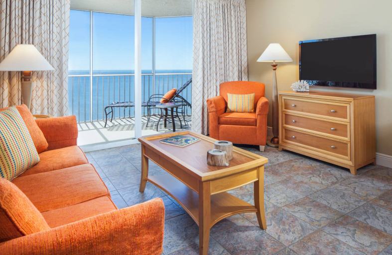 Hotel room living area with orange couches, tables, TV, dresser, and balcony